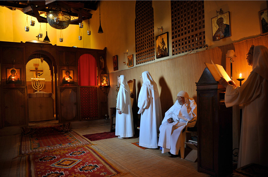 During vespers, the sisters of the oriental Catholic Monastery of the Visitation sing Psalms in both French and Arabic. A menohra casts a glow on the crucifix, Tazert, 2011