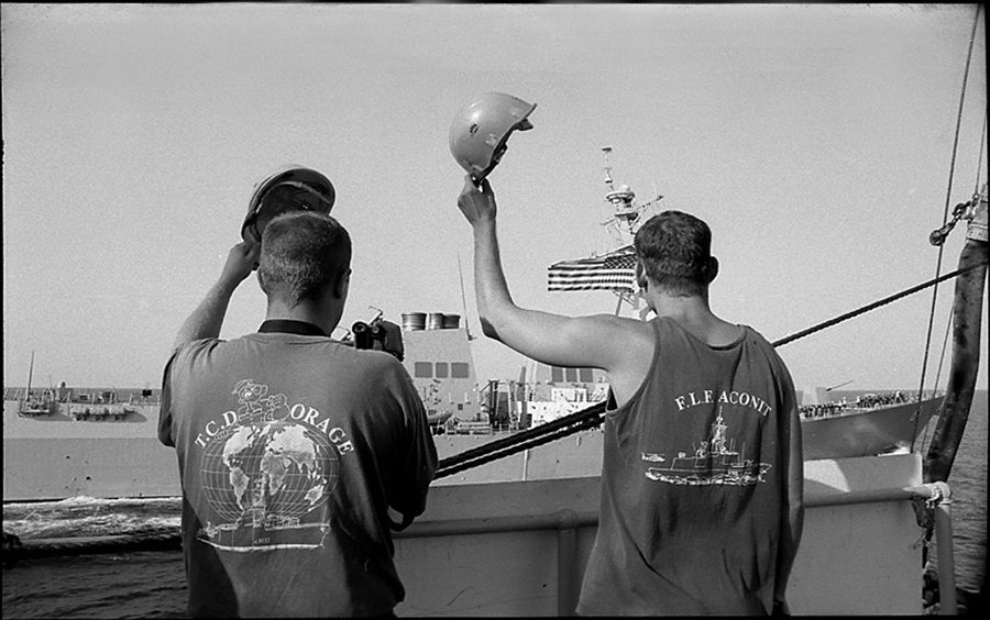 Two crewmen of the VAR salute the crew of destroyer USS Winston S. Churchill after supply